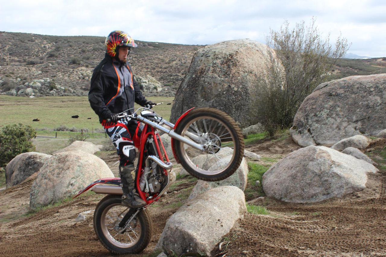 Riding a Motorcycle Over a Big Rock